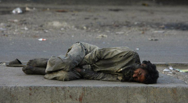 A homeless man sleeps on a street divider early morning in Lahore April 28, 2009.  REUTERS/Mohsin Raza  (PAKISTAN SOCIETY)