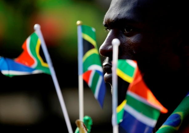 A man holds South African national flags as he stands in a queue at the Union Buildings in Pretoria December 12, 2013. Thousands of people lined the streets to view the body of  former South African President Nelson Mandela.   REUTERS/Kevin Coombs (SOUTH AFRICA - Tags: POLITICS OBITUARY SOCIETY) - RTX16EYF